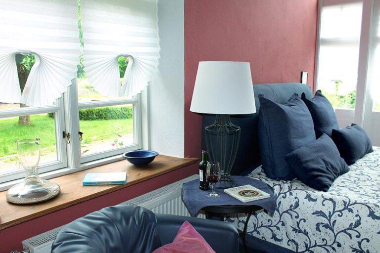Urlaub im Landhaus Kanzler in Thandorf - Blick auf das Doppelbett im roten Zimmer mit Lese-Ecke